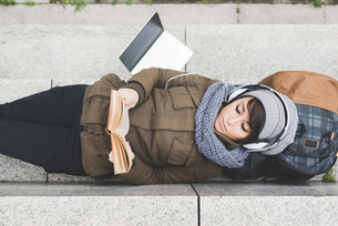 Overhead view of female backpacker lying on back reading book on wallの写真素材 [FYI03582678]