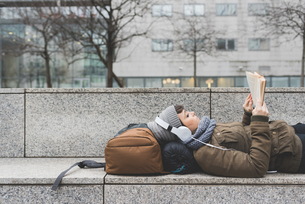 Female backpacker lying on back reading book on wallの写真素材 [FYI03582679]
