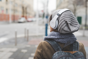 Rear view of female backpacker listening to headphones in empty cityの写真素材 [FYI03582680]