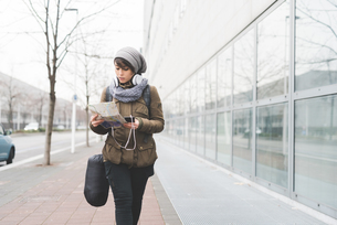Female backpacker with smartphone looking at map on city sidewalkの写真素材 [FYI03582681]