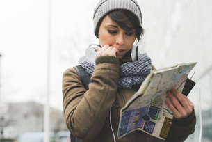 Female backpacker biting nails and looking at map in cityの写真素材 [FYI03582685]