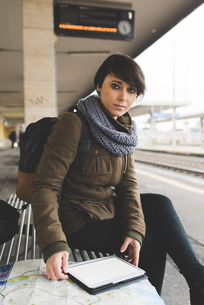 Portrait of female backpacker with map and digital tablet on railway platformの写真素材 [FYI03582689]