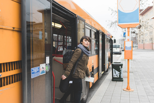 Female backpacker exiting bus at city stationの写真素材 [FYI03582690]