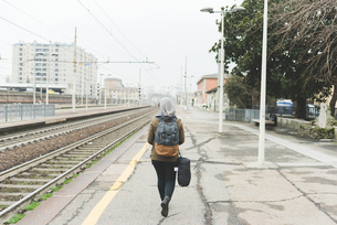 Rear view of female backpacker on railway platformの写真素材 [FYI03582692]