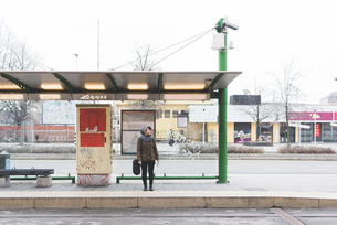 Female backpacker standing at city bus stationの写真素材 [FYI03582696]