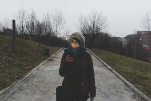 Female backpacker walking in city park at dusk looking at smartphoneの写真素材 [FYI03582701]