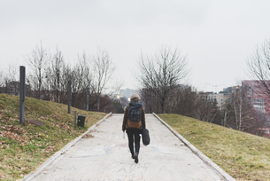 Rear view of female backpacker walking alone in city parkの写真素材 [FYI03582705]