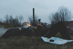 Female backpacker lying in city park at night looking at smartphoneの写真素材 [FYI03582706]