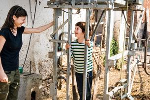 Female organic farmer with boy in animal stall at dairy farmの写真素材 [FYI03582766]