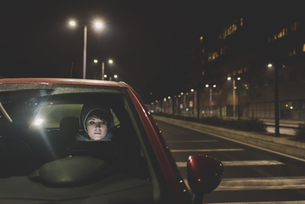 Woman looking out of car windscreen on city roadside at nightの写真素材 [FYI03582793]