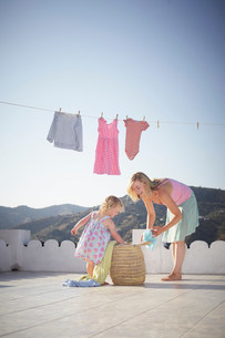 Mother and daughter hanging washingの写真素材 [FYI03583023]