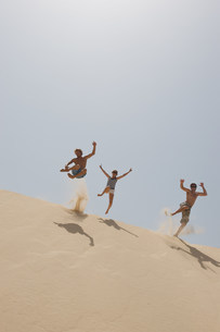 Friends jumping over a big sand duneの写真素材 [FYI03583209]