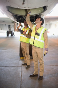 Aircraft workers checking airplaneの写真素材 [FYI03583262]