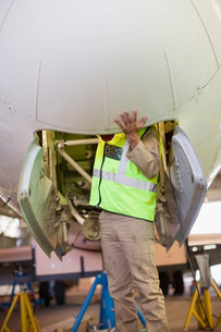 Aircraft worker checking airplaneの写真素材 [FYI03583277]
