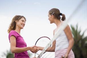 Girls shaking hands on tennis courtの写真素材 [FYI03583299]