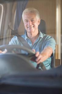Smiling older man driving RVの写真素材 [FYI03583356]