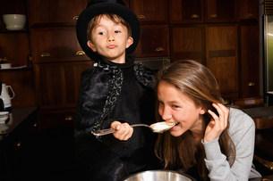 Girl tasting boy magician's cookingの写真素材 [FYI03583419]