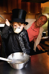 Boy magician tasting his cookingの写真素材 [FYI03583421]