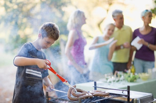 Boy barbecuing sausage outdoorsの写真素材 [FYI03583463]