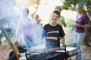 Boy barbecuing sausage outdoorsの写真素材 [FYI03583468]