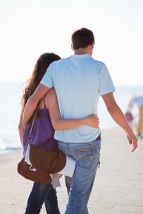Couple walking and hugging on beachの写真素材 [FYI03583623]