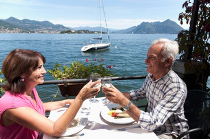 Older couple toasting with wine outdoorsの写真素材 [FYI03583660]