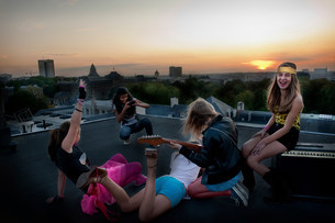 Teenage girls relaxing on roofの写真素材 [FYI03583822]