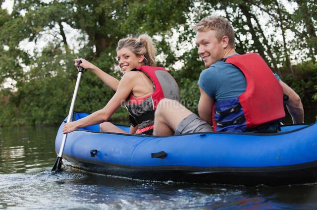 Smiling couple kayaking in creekの写真素材 [FYI03583845]