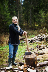 Woman chopping firewood in forestの写真素材 [FYI03583854]