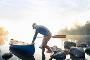 Man pushing canoe into still lakeの写真素材 [FYI03583856]