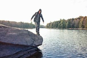 Man walking on boulder by still lakeの写真素材 [FYI03583859]