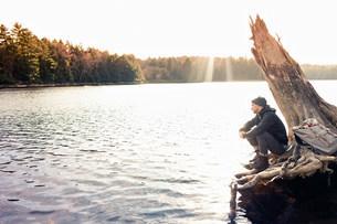 Man sitting on boulder by still lakeの写真素材 [FYI03583860]
