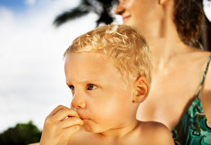 Boy sitting on mothers lap outdoorsの写真素材 [FYI03583988]