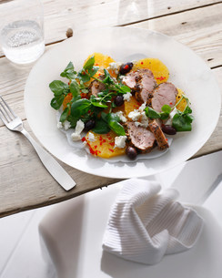 Plate of pork with pickled orange saladの写真素材 [FYI03584236]