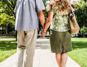 Older couple holding hands in parkの写真素材 [FYI03584262]
