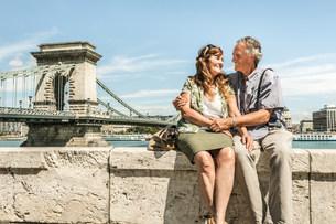 Older couple sitting on bridgeの写真素材 [FYI03584275]