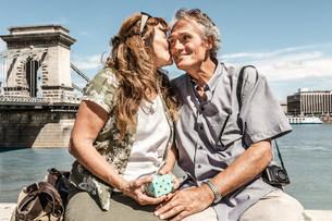 Older couple kissing on bridgeの写真素材 [FYI03584278]
