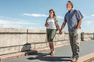 Older couple holding hands on bridgeの写真素材 [FYI03584279]
