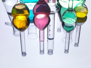 Beakers with liquids on reflective tableの写真素材 [FYI03584328]