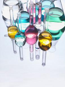 Beakers with liquids on reflective tableの写真素材 [FYI03584329]