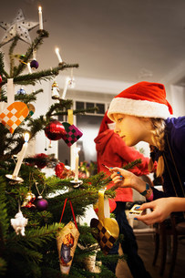 Girl decorating Christmas treeの写真素材 [FYI03584463]