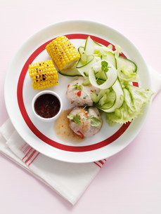 Plate of corn with cucumber saladの写真素材 [FYI03584600]