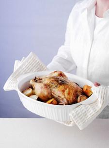Woman holding dish of roast chickenの写真素材 [FYI03584608]