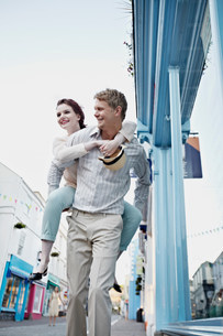 Man carrying girlfriend on city streetの写真素材 [FYI03584733]