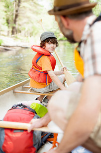 Father and son packing canoe on riverの写真素材 [FYI03584848]