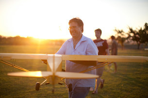 Men playing with toy airplane in parkの写真素材 [FYI03585426]