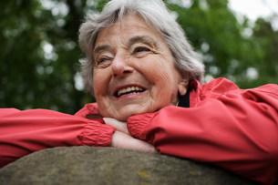 Older woman resting on rock in parkの写真素材 [FYI03585460]