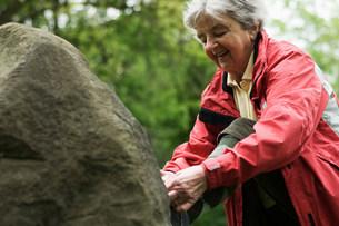 Older woman tying shoe on rock in parkの写真素材 [FYI03585461]
