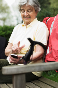 Older woman using cell phone on benchの写真素材 [FYI03585463]