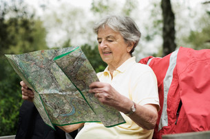 Older woman reading map in parkの写真素材 [FYI03585468]